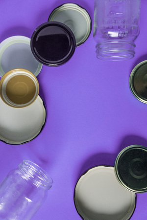 Recycling glass jar lids for reuse of single use items; Zero no waste recycle program campaigns; Recyclable concept on blank empty copyspace, text room space for copy on vertical purple background.