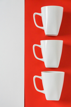 3 white winter coffee cup mugs lined up in a row for a break time meeting; Copyspace with empty room space for copy text on red vertical background; Christmas holiday or Valentines.