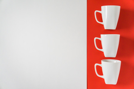 3 white winter coffee cup mugs lined up in a row for a break time meeting; Copyspace with empty room space for copy text on red horizontal background; Christmas holiday or Valentines.