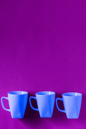 3 blue winter coffee cup mugs lined up in a row for a break time meeting; Copyspace with empty room space for copy text on purple vertical background