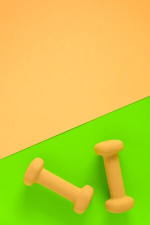 Fitness equipment with womens yellow weights/ dumbbells isolated on a lime green and yellow pink background with copyspace (aka empty copy text room space).