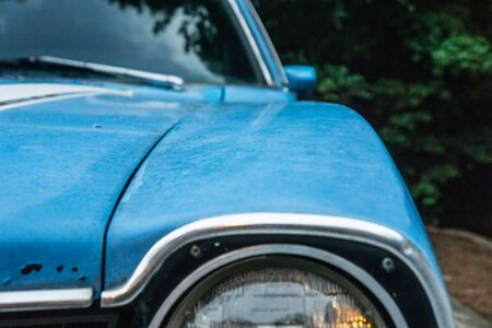 Close up of vintage blue car's old headlamp. Parked and surrounded by green trees foliage outside. No person, but close-up of driver's side with rear view mirror and windshield. Blank empty copy space