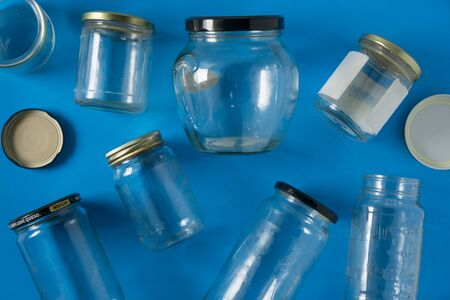 Transparent glass jars with lids isolated on blue background, top view flat lay recycling concept for environmental awareness. Segregated recyclables mock up conceptual idea for junk waste disposal.