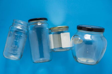 Isolated glass jars laid flat and center on blue background. Recycling program or campaign image with an assortment of top view containers. Conceptual awareness for reusable recyclables.