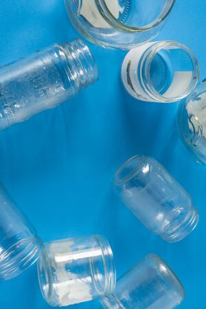 Isolated open glass jars laid flat on blue background - blank empty room space room for text, copy, or center copyspace. Recycling program or campaign image with an assortment of top view containers.