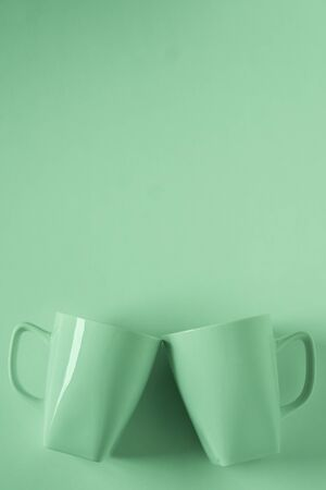 2 monochromatic green coffee mugs on green background clinking in cheers with blank empty room space for text, copy, or copyspace. Modern top view concept of two cups with solid background backdrop. Imagens