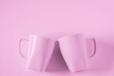 2 monochromatic pink coffee mugs on pink background clinking in cheers with blank empty room space for text, copy, or copyspace. Modern top view concept of two cups with solid background backdrop. Imagens