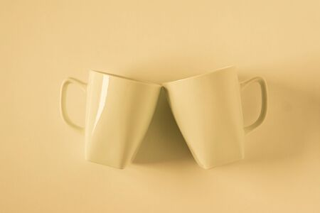 2 monochromatic yellow coffee mugs on yellow background clinking in cheers with blank empty room space for text, copy, or copy space. Modern top view concept of two cups with solid background backdrop.