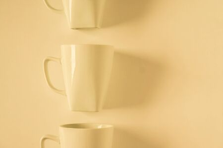 One singled out monochromatic yellow coffee mug lined up in a row on yellow background with blank empty room space for text, copy, or copy space. Modern top view concept with solid background backdrop