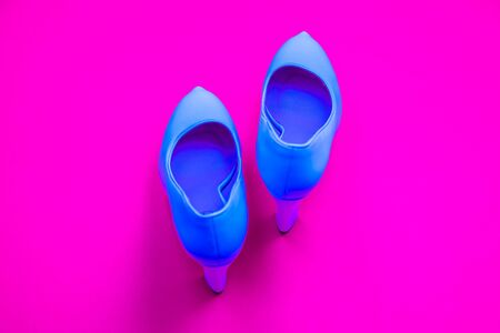 Blue high heeled shoes on pink purple background - top view concept - blank empty room space for text or copy. Classic dress up fashion. Heels pointing up