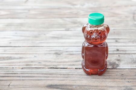 Healthy organic natural sweetener, raw honey - from bees. Golden brown liquid in bear shaped bottle with green cap. Isolated on solid wooden background with blank empty room space for text or copy. Stok Fotoğraf