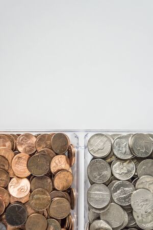 Isolated organized loose coin change on bottom side, white background, blank empty room space for copy or text on top. Financial organization money concept, top view of pennies, nickels, and quarters.