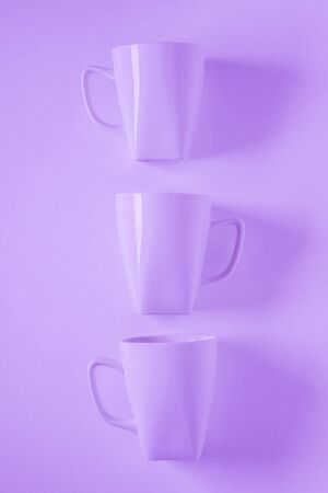 3 monochromatic purple coffee mugs lined up in a row on violet background with blank empty room space for text, copy, or copy space. Modern top view concept of three cups, solid background backdrop 版權商用圖片