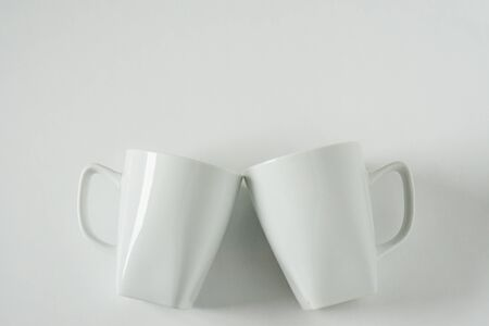 2 monochromatic white coffee mugs on white background clinking in cheers with blank empty room space for text, copy, or copy space. Modern top view concept of two cups with solid background backdrop.