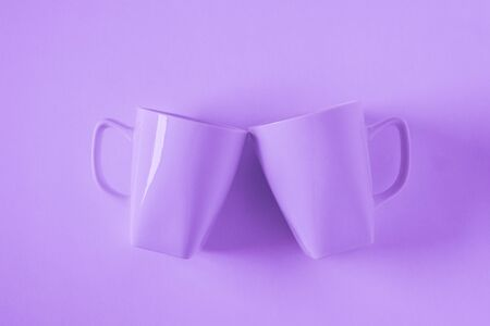 2 monochromatic purple coffee mugs, purplish background clinking in cheers - blank empty room space for text, copy, or copy space. Modern top view concept of two cups with solid background backdrop.