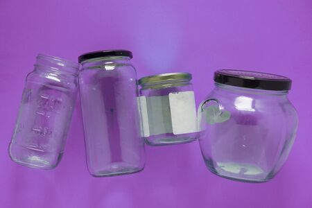 Isolated glass jars laid flat and center on violet purple background. Recycling program or campaign image with an assortment of top view containers. Conceptual awareness for reusable recyclables. Banco de Imagens