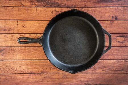 Traditional heavy duty cast iron skillet on wooden surface - isolated top view with copy space. Black cooking utensil - campfire cookware and kitchenware. Kitchen equipment that lasts a lifetime. Stockfoto