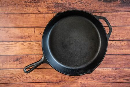 Traditional heavy duty cast iron skillet on wooden surface - isolated top view with copy space. Black cooking utensil - campfire cookware and kitchenware. Kitchen equipment that lasts a lifetime.