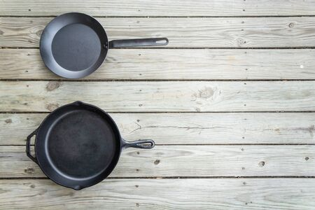 Cookware battle with cast iron vs vs carbon steel skillet pan cooking options - blank empty room for text or copy space on right. Traditional versus new healthier option.