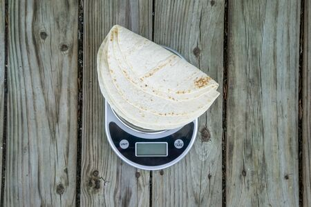 Low carb tortillas on a scale on wooden background - trending health food. Top view from overhead. Keto friendly. Blank empty room for text or copy space.