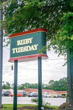 Loganville, GA - July 13th 2019: Street sign of Ruby Tuesday restaurant with road and cars in background. American franchise located off highway 78. Features all you can eat salad bar