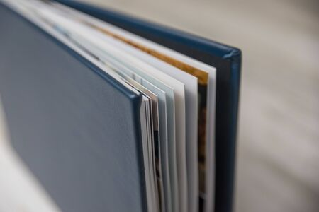 Side view close up of thick and rigid wedding album pages in a book with navy blue leather cover. Blank empty room space for text or copy.
