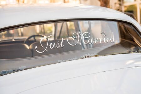 Bullet holes in car windshield with Just Married sign for newlyweds. Get away car for escaping the wedding.