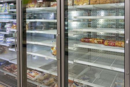 Atlanta, GA / USA - 04/02/20: Empty freezer shelves at Publix featuring frozen food shortage including organic vegetables, pizza, and junk food during Covid-19 corona virus.