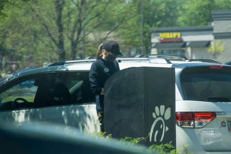 Kennesaw, GA / USA - 04/02/20: Young youthful fast food worker working at Chick-fil-a drive through amidst cars take orders with tablet.