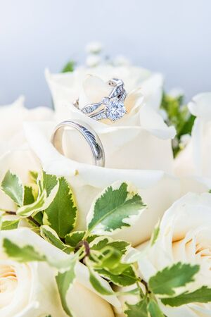 Engagement ring paired with wedding bands, resting on a bouquet of white roses Stock Photo