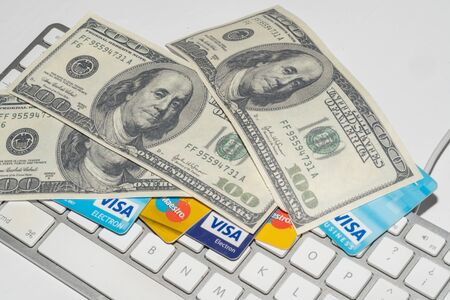 Online Commerce, Ecommerce, credit and debit cards with dollars and a keyboard.