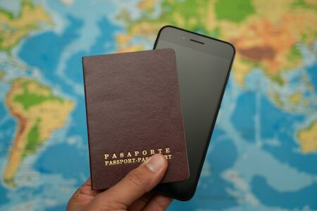 Man holds with his hand the passport and smartphone, world map. Travel concept