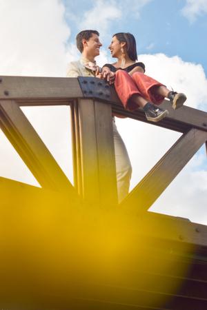 Pareja de novios se miran apasionadamente, llenos de amor, en mitad de un puente de madera