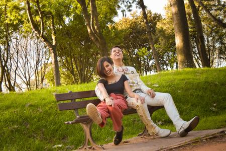 Pareja de novios felices contemplando el paisaje desde una banca de madera en el bosque Imagens