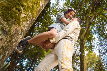Young mariachi raises in his loving arms his girlfriend in the middle of a forest