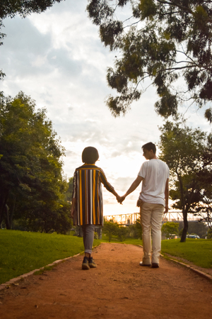 Couple of bride and groom walking, holding hands, during sunset in a forest of Bogotá