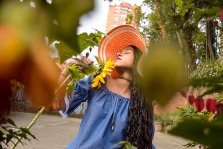 As if she were a muse of inspiration, this is how this beautiful Latina looks very attractive who seems to be seducing the sunflower she carries in her hands.