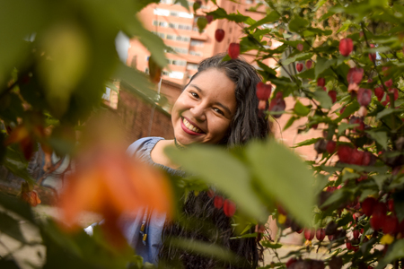 Through a foliage of leaves and flowers you see a smiling and beautiful young woman. Imagens