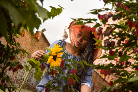 Beautiful young woman with a sun hat pensively looks at a sunflower flower, she is surrounded by a foliage of leaves and flowers