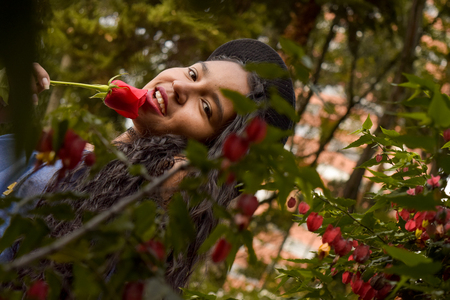 Beautiful and seductive young woman with hat, passionately holds a rose in her mouth. She looks at us with madness through a foliage of leaves