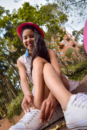 Teen girl with dress and hat, is sitting tying her tennis on a stairs of a city park Imagens