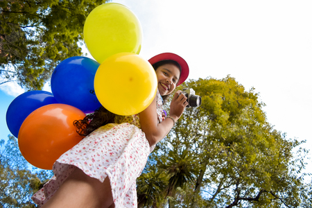 Young woman photographer smiles while holding many colorful balloons on her back, in the middle of trees
