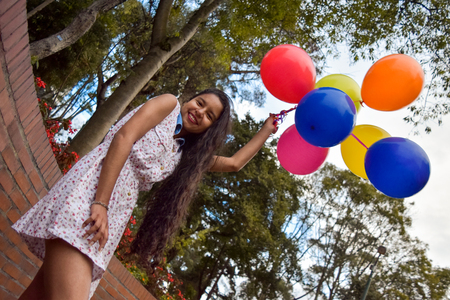 Beautiful young girl walks with a bunch of collofull balloons by a city park during sunset Imagens
