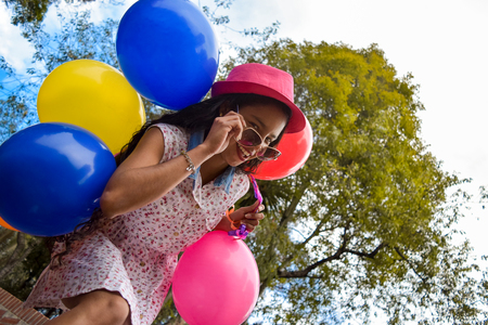 Beautiful young latin woman with dress, hat and sunglasses carries on her back many colored balloons while walking in an urban park