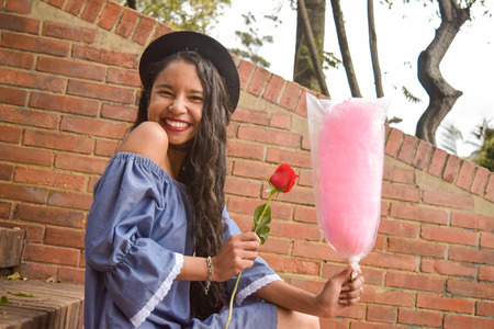 A young, beautiful and in love young girl with a dress of bare shoulders and a fedora hat just received a red rose and a cotton candy. She is very happy and radiant with joy.