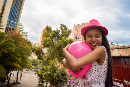 Tender teenage woman with dress and a pink hat, hugs a balloon while smiling at us in the middle of an urban park