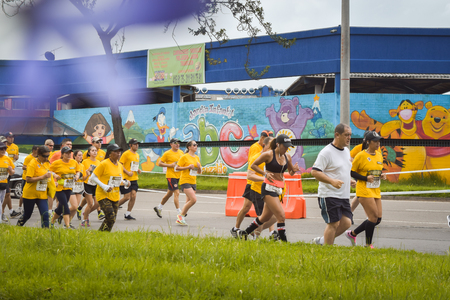 Bogota Colombia. (May 06, 2018). The athletes cross trotting in a group together with a garden with murals painted with children's cartoons. Foto de archivo - 121982059