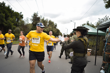 Bogota Colombia. (May 06, 2018). A man and a police patrol collide their hands as a sign of friendship while he runs by.