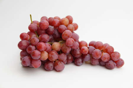 Fresh and ripe red grapes isolated in white background. Bunch of raw and juicy grapevines ..