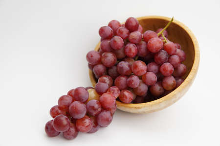 Fresh and ripe red grapes in a wooden bowl, isolated in white background. Bunch of raw and juicy grapevines ..